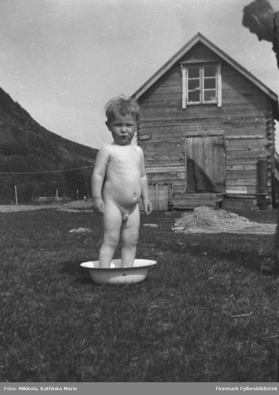Willy Olsen bader i et vaskevannsfat på gårdsplassen på Mikkelsnes. I bakgrunnen melkebua på gården, og foran bua ligger en stor fiskenot, antakelig under greiing. Willys far, Per Sivle Olsen, i øvre høyre bildehjørne