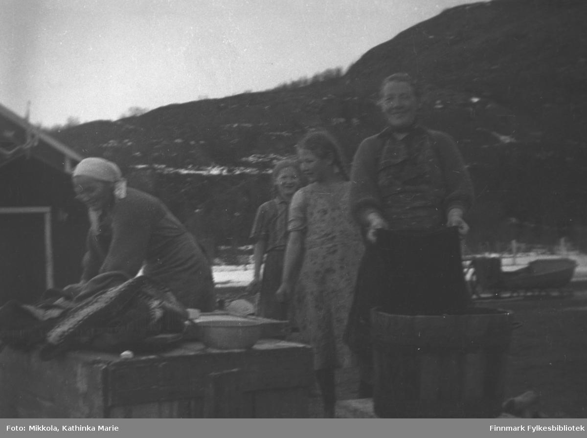 Søstrene Mikkola vasker klær utendørs. Klærne ligger stablet på benken til venstre, her er store baljer og mindre vaskevannsfat. Fra venstre: Marine, Kari, Ingrid og Synnøve