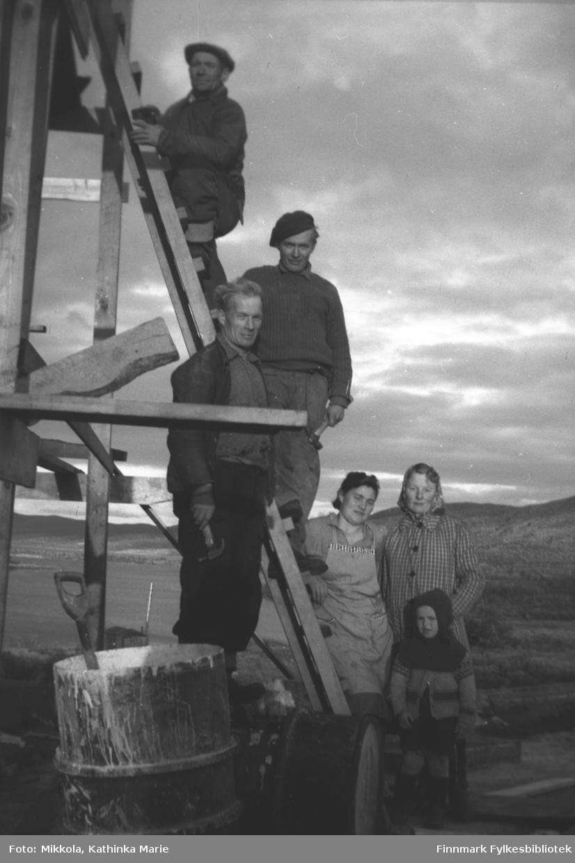 Huset til familien Mathisen ble bygget i 1946, ved Munkelv bru. Mannen øverst i stigen er Per Mathisen. De andre er fra venstre: Frans Aksel Labahå med hammer, så Trygve Mathisen, Ella Mathisen, Mildrid Jerijærvi (gift Abrahamsen). Den lille gutten foran er Mathis Magga.