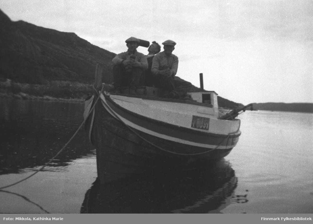 Mindre motorbåt fortøyd ved sjøsiden på Mikkelsnes. Båten har registreringsnummer F63SV. Tre menn sitter ombord, to av dem med flasker. Fra venstre: Arvid, Storm og Leif Mikkola. Bildet har en rolig stemning av avslapning etter strev