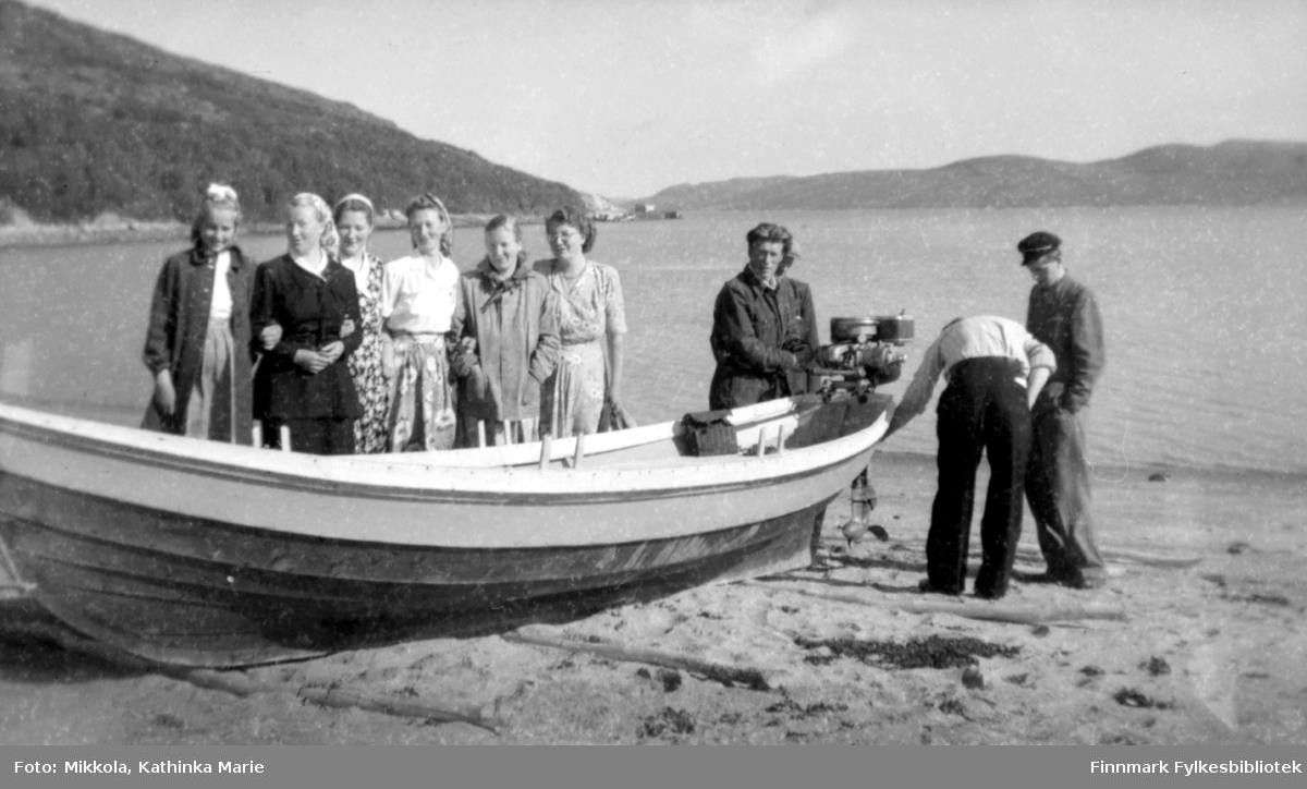 Trebåt trukket opp i fjæra ved Mikkelsnes, det ligger trestokker under kjølen for at båten ikke skal grave seg ned i sanda. Båten har to sett tollepinner og påhengsmotor. Ved båten, fra venstre: Ukjent, Herlaug, Kari og Marine Mikkola, ukjent, Ingrid Mikkola, Sverre Olsen Lie, ukjent mann med ryggen til kamera, Mikkel Mikkola helt til høyre i bildet