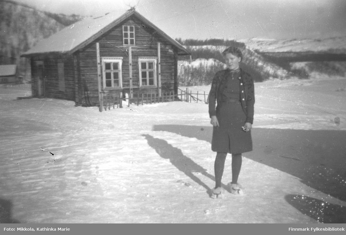 Gudrun Mikkola fotografert i snøen foran gamlestua på eiendommen Nordmannseng. Eiendommen ligger ved kirka i Neiden. Denne tømmerstua ble også brukt som skole i noen peridoer