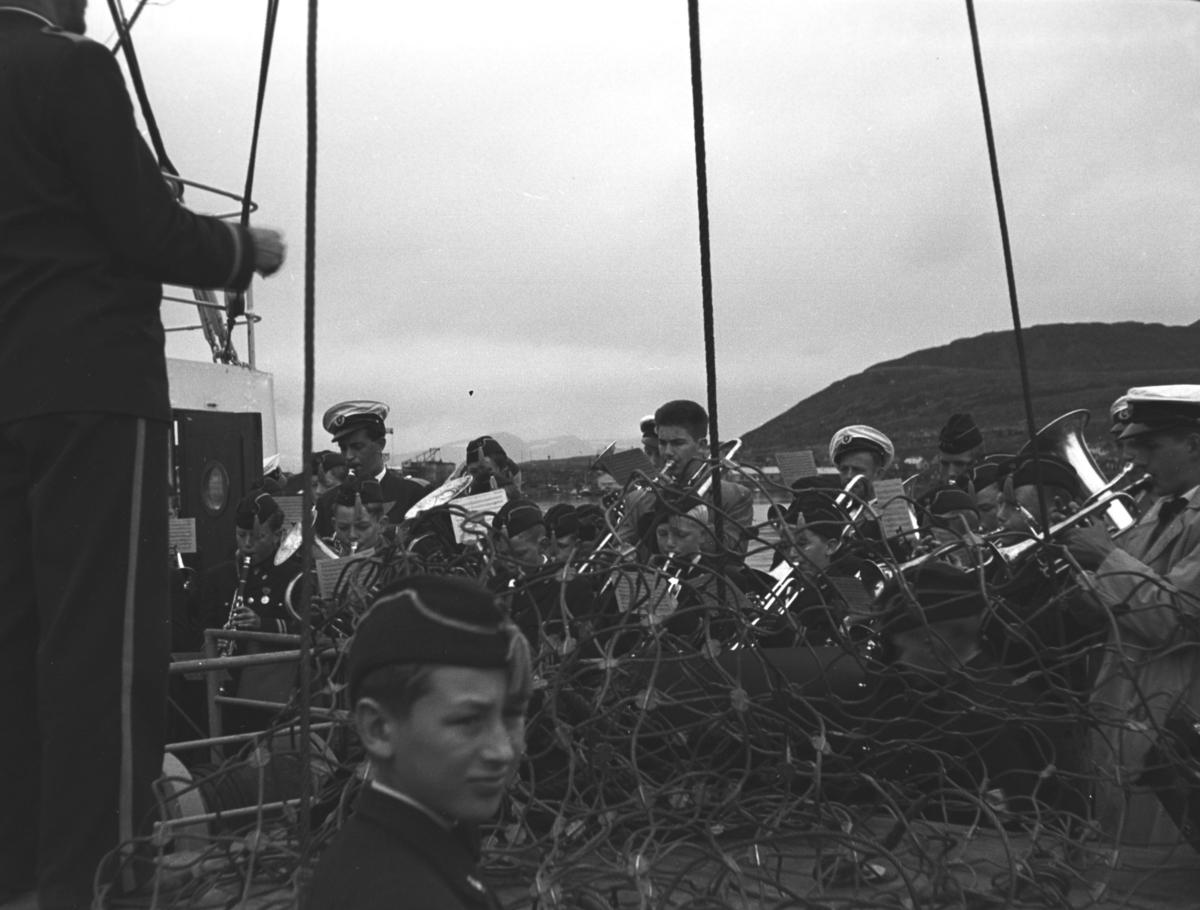 Et musikkorps spiller på dekket av en båt som muligens er Hurtigruta. Personer og sted er ukjent, men fjellet i bakgrunnen minner sterkt om Vardfjell så det kan være at båten ligger ved D/S-kaia i Hammerfest.