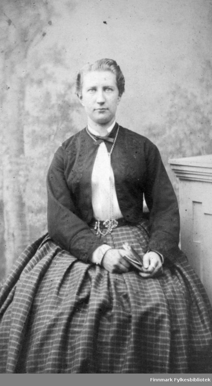Portrett av en dame som sitter i en stol. Hun har et rutet skjørt, tynn mørk jakke og hvit bluse. Et kjede henger rundt halsen hennes.