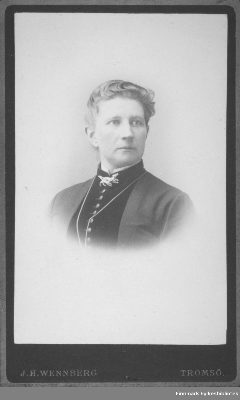 Portrett av en dame i mørk bluse og en tynn jakke over. Hun har en brosje i halsen og et kjede henger nedover brystet. Portrettet er tatt i J. H. Wennberg atelier i Tromsø.
