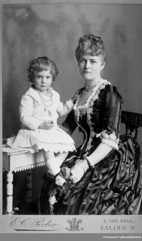 Portrett av Philippa Desiree (f.til Schwensen) Temple med sitt barn Mary Penelope Temple. Barnet sitter på en hvitt bord med utskjæringer og dreiemønster. Hun har en hvit kjole, hvite strømper og et perlekjede rundt halsen. Damen har en mørk kjole med svake striper og blonder på armene og i halsen. Hun har et kjede rundt halsen og armband rundt håndleddet. Philippa Desiree født 1853 i Hasvik og døde 1924 i Middlesex, England. Hun var gift med George Theodore Temple (1847-1935). Portrettet er tatt av E.C. Porter i London.