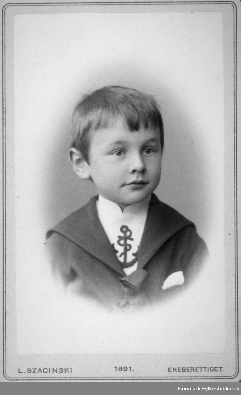 Portrett av en gutt. Han har en mørk jakke med bred krage og lommetørkle i brystlomma. Den hvite skjorta hans har et ankermønster foran. Potrettet er tatt hos kgl. hoffotograf L. Szacinski.