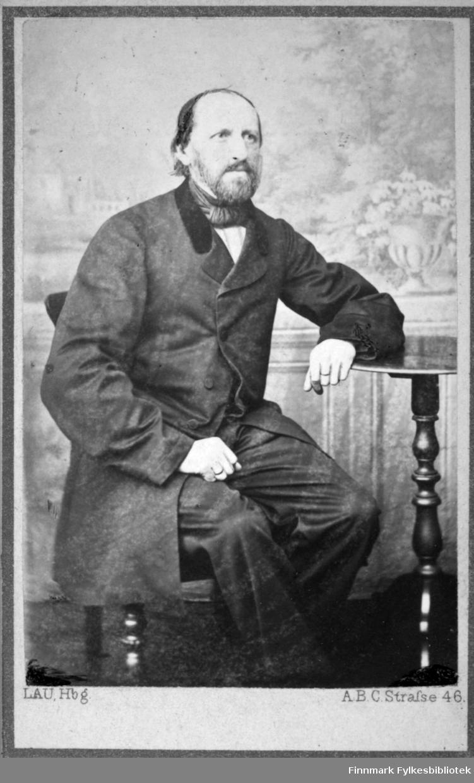 Portrett av en mann sittende i en stol. Han er iført mørk dress og hvit skjorte. Foran han står et lite, rundt bord med utskjæringer/dreiemønster på foten/sokkelen, som han hviler venstre arm på. På veggen bak han henger et stort maleri.