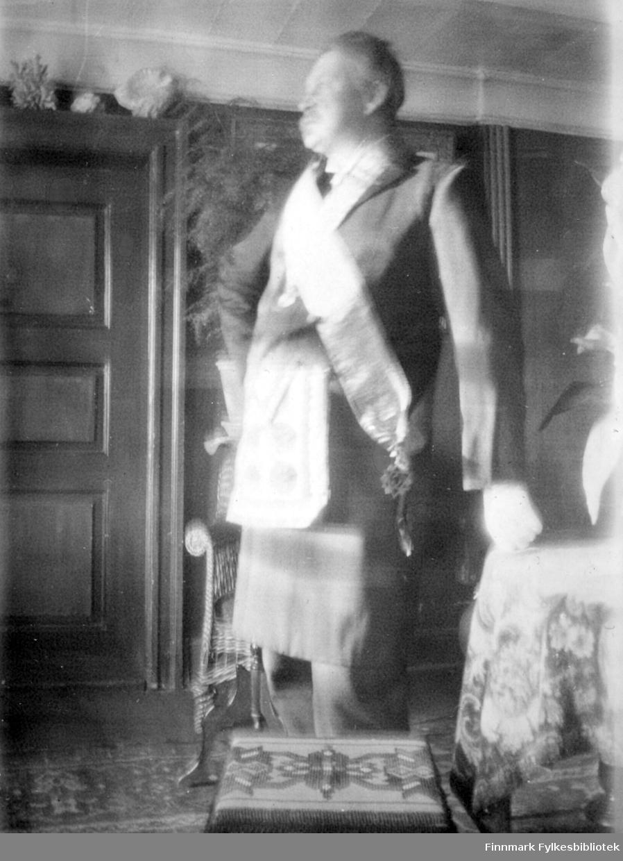 Arthur Buck står i stram giv akt i et rom. Han har en forholdsvis mørk frakk på seg, buksen er av samme farge. Han har også hvit skjorte og slips. I tillegg har han et ordenbånd gående fra høyre skulder og ned mot mot hoften. Bak han står en kurvstol og foran en krakk eller en kasse. Den har mønster på toppen. Et rundt bord står til høyre med en mønstret, stor duk på. Man kan også se en liten del av en blomst oppå. Veggen i bakgrunnen på bildet er av ganske mørkt tre med speil og en blomst og noe annet står helt øverst til venste. Et mønstret gulvteppe ses nederst på bildet.