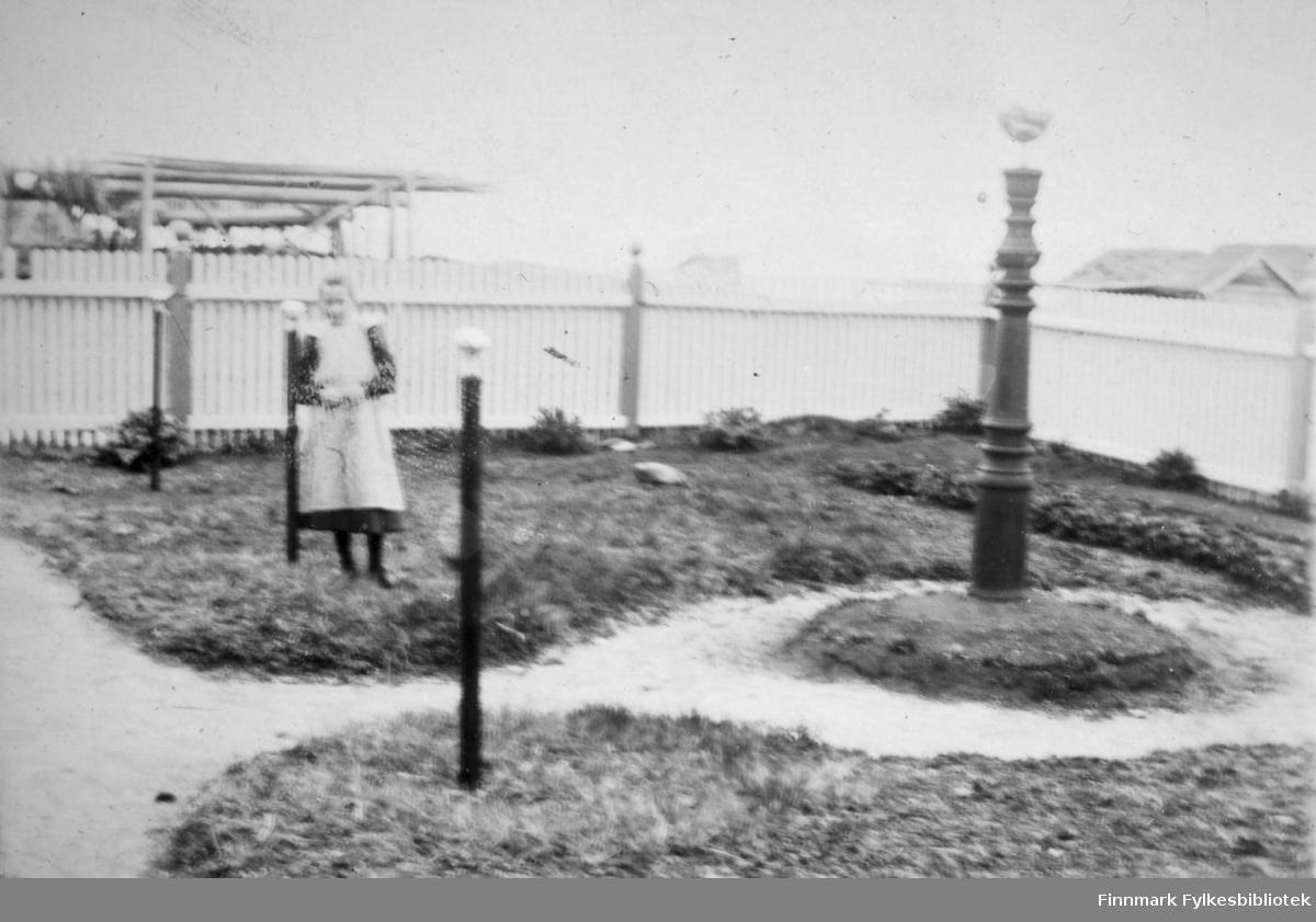 En jente fotografert i Arthur og Kirsten Bucks hage på Hasvik. Hun har en mørk kjole med et hvit, helforkle på seg. Det står flere søyler i hagen, Den lengst til høyre på bildet er ganske stor og har dreie-mønster. Den står på en egen rund jordflekk med en slags gangsti rundt. Et stort, hvitmalt stakittgjerde står rundt området og det har tykke stolper med kuler på toppen. Til høyre på bildet kan deler at et hustak ses over gjerdet og til venstre, utenfor gjerdet, står noe som kan være en fiskehjell.