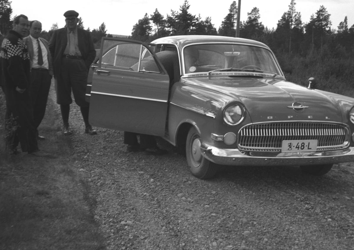 """Tre personer står ved siden av en bil, Opel Kaptein årsmodell 1956-57. Det tilsier at bildet tidligst kan være tatt høsten 1955. Registrert på uvanlig finsk skilt, med den finske riksløven først og bokstaven bakerst. Tyder på at den er statlig, med spesiell status, kanksje """"Riksdagsbesøk""""."""
