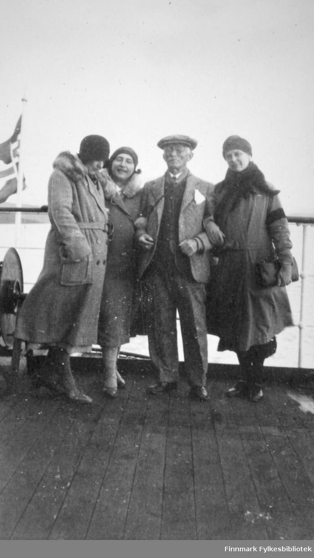 Fire personer, tre kvinner og en mann, poserer på et båtdekk. Mannen har dress, mørk genser, hvit skjorte og slips. Han har også sixpence på hodet. Damene har lange kåper med pelskraver. Alle tre har luer på hodene. Et hvitt metallrekkverk med sort kant står rett bak dem. En flaggstang med det norske flagg heist til venstre på bildet, noe som tyder på at det er på hekken på fartøyet. Dørken der de står er av tre.