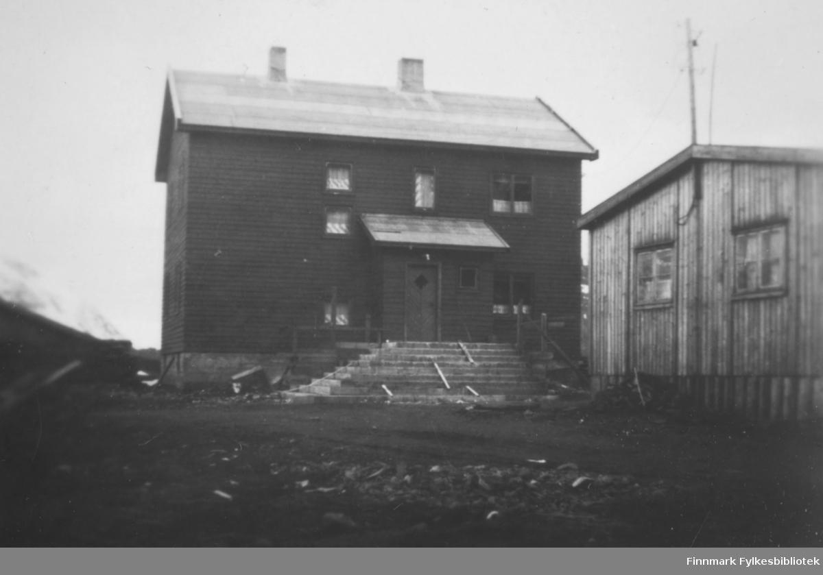 Et stort hus med en bred trapp. Et vindfang står midt på langveggen. Huset er malt med en mørk farge og har vinduer av ulik størrelse på langveggen, og to vinduer på røstveggen. To skorsteiner står på det pappkledte taket. En lav grunnmur har to små vinduer og til venstre for huset ligger en stabel med ved/materialer. Bakken foran huset består stort sett av jord/grus. Til høyre på bildet ses røstveggen på et lite bygg. Det har stående, umalt panel og to sprossevinduer. En el-stolpe ses bak det.