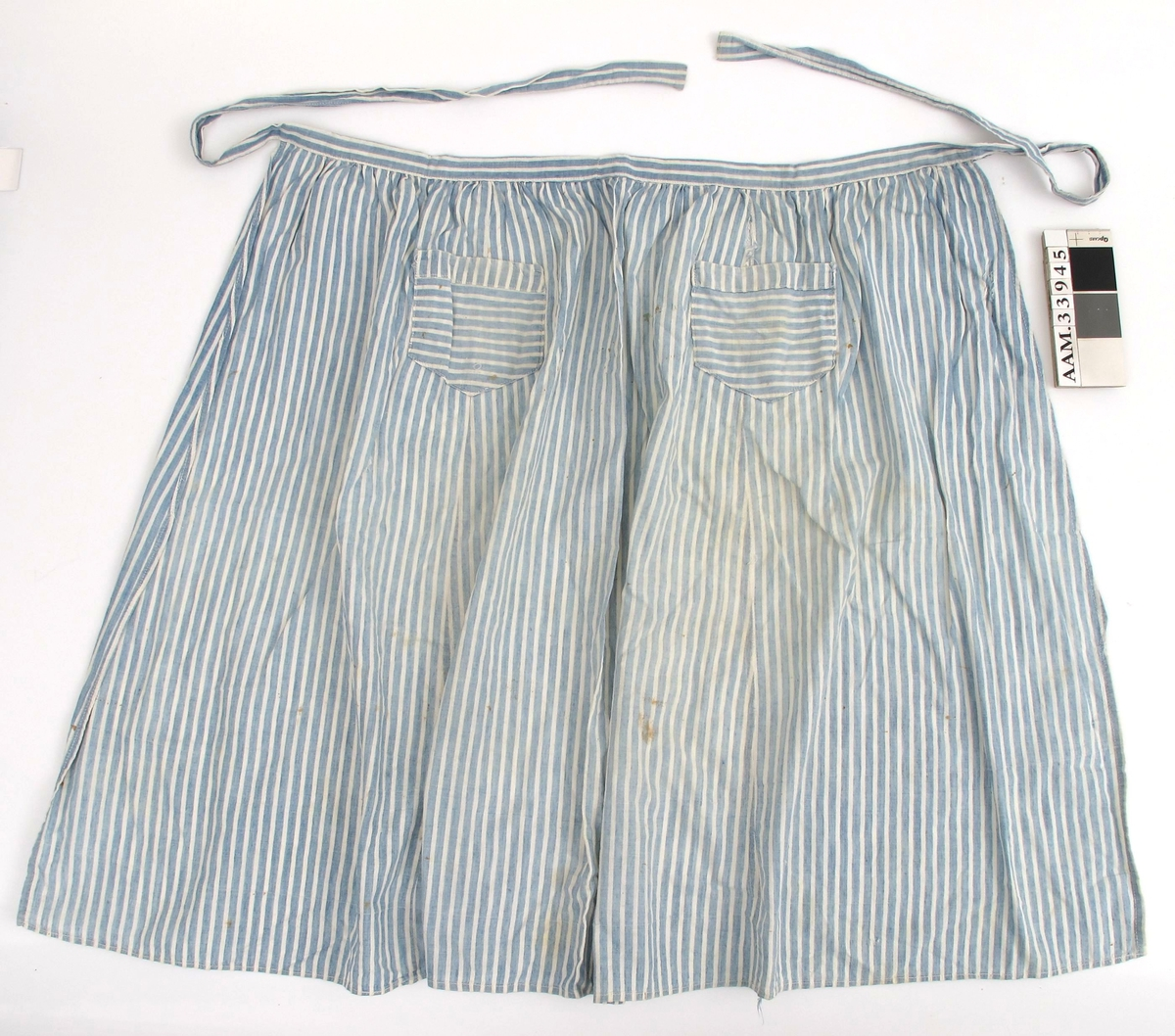 Forkle av stripet bomullstoff i blått og hvitt.  Hjemmesydd. Liten lomme med stripene plassert på tvers.