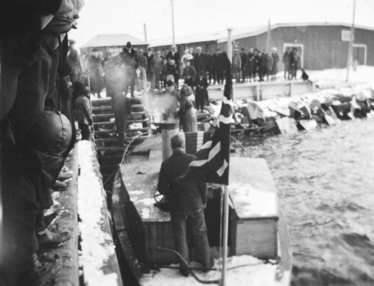 Kronprins Olav og Kronprinsesse Martha på besøk i Vadsø 1934. På bildet er de i en båt ved havna. Det står mange folk på kaia