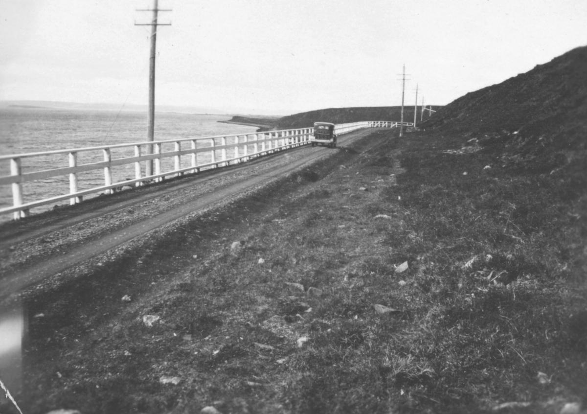 En bil på veien, muligens ved Mortensnes. Langs kanten mot sjøen, er det satt opp et rekkverk. Det står veistikker på høyresiden