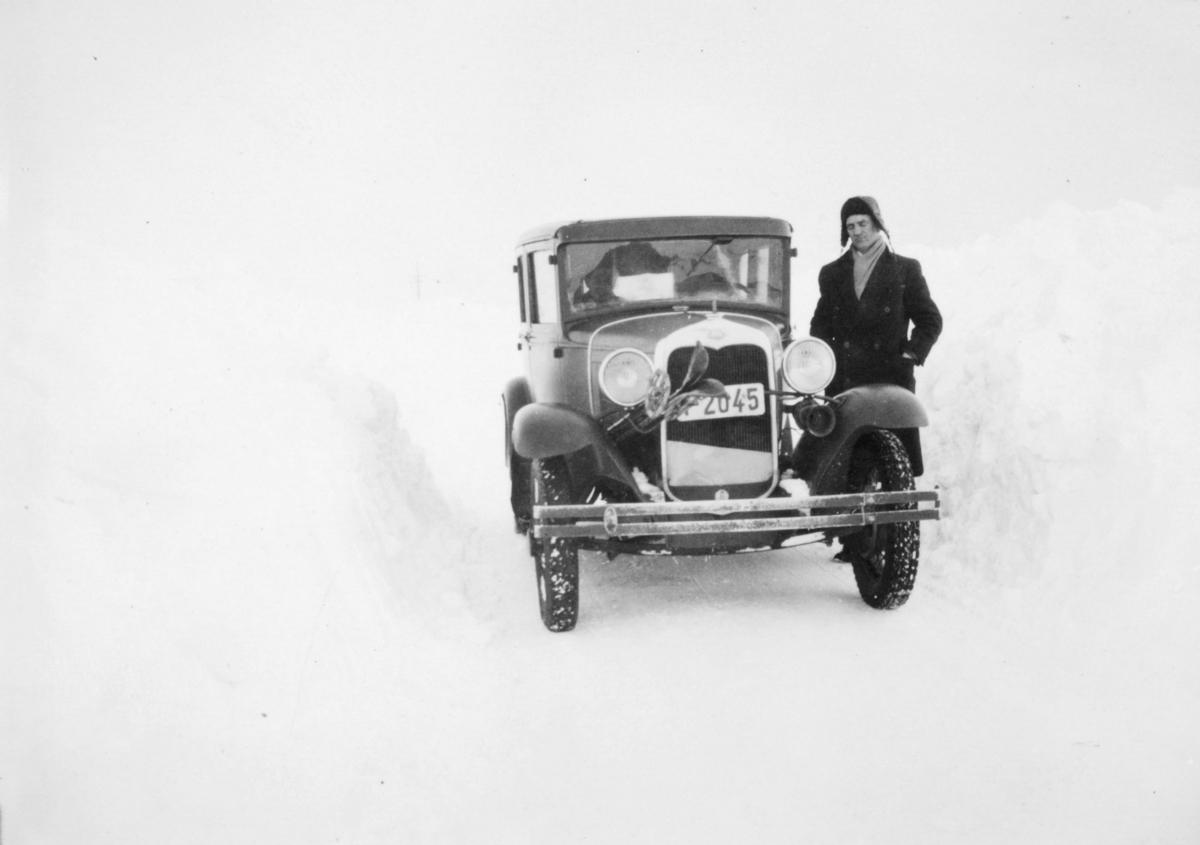 En mann står ved siden av en Ford A-modell fra 1930. Det er vinter og sne. Mannen er kledt i frakk . Han har lue og skjerf på seg. Bilnummeret er Y2045.  I Norges Bilbok 1935 står nummeret registrert på drosjeeier Georg S. Dahl i Vadsø.