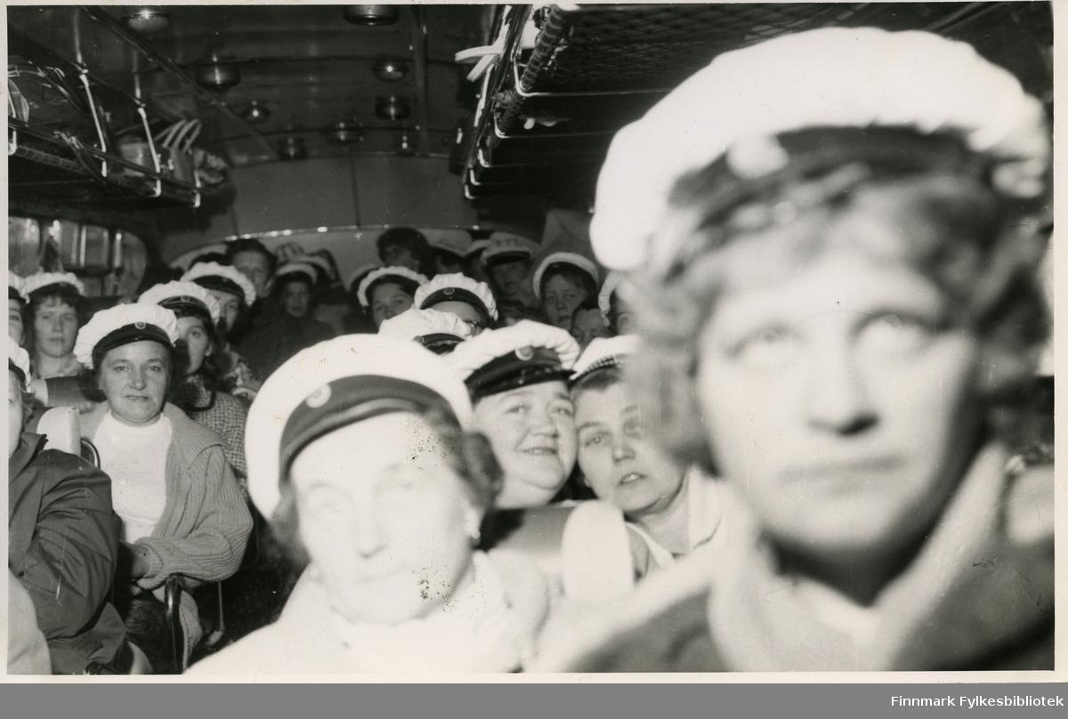 Vadsø damekor i bussen på tur til Berlevåg (muligens rundt 17. mai) 1962. Kvinnene har på seg en hvit hatt, trolig kor uniform. I bussens håndbagasje hylle kan man se vesker og kofferter av forskjellige slag. Damene har på seg jakker og gensere.