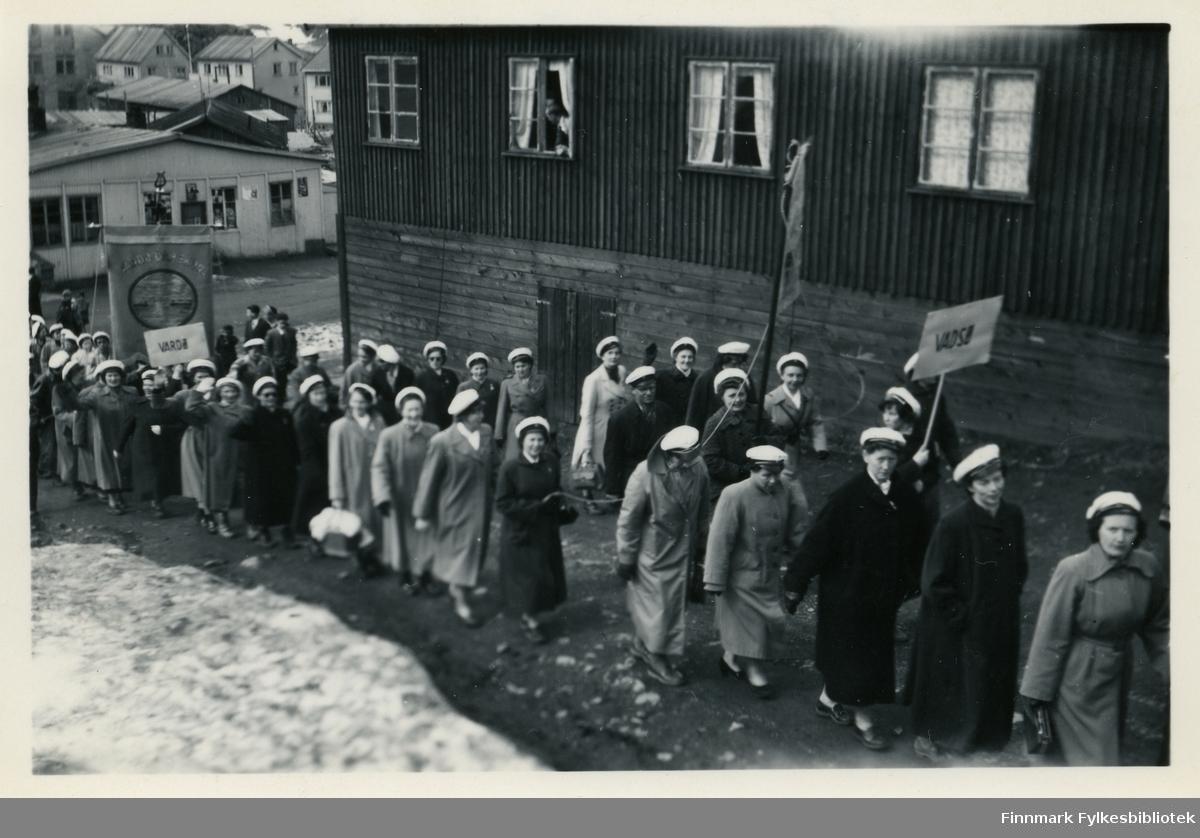 Korene defilerer i tog. Vadsø damekor i ledelsen, Vardø damekor følgende etter. De bærer på faner. På seg har damene kåper og hvite hatter. Ved siden av toget er det et hus med vinduer. I vinduene kan man se gardiner. Det er sne på bakken.