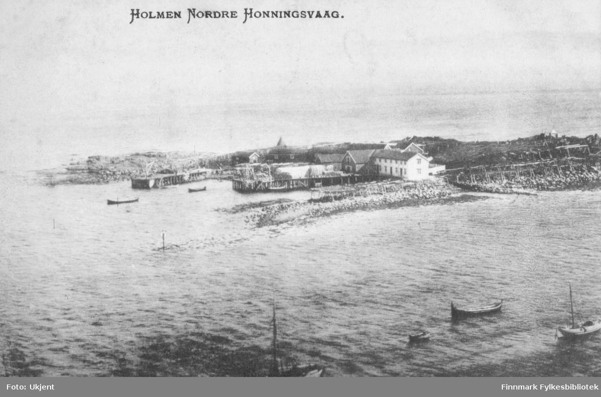 'Holmen Nordre Honningsvaag', står det trykket på dette postkortet. På bilde kan man se en havn med kaier og hus. Enkelte båter ligger ute på havet. I området ligger det flere hjeller.