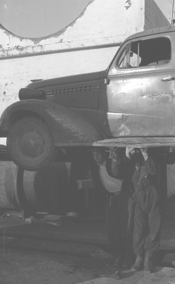 En Chevrolet, årsmodell 1938,  er heist opp på en bukk og to menn står under den. Personer og sted er ukjent.