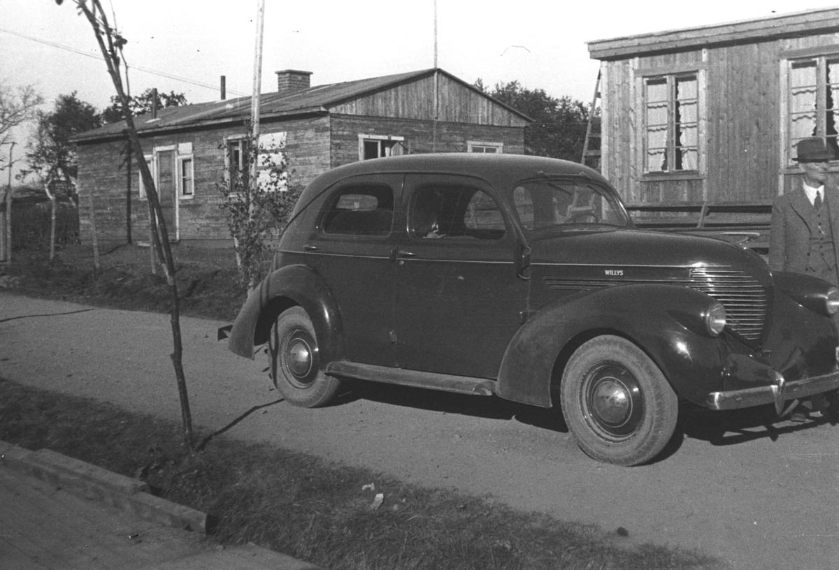 En bil (Willys 1937-38-modell) står parkert utenfor to små hus eller hytter. Stedet er ukjent, men iflg. informanten kan det være i Tana.