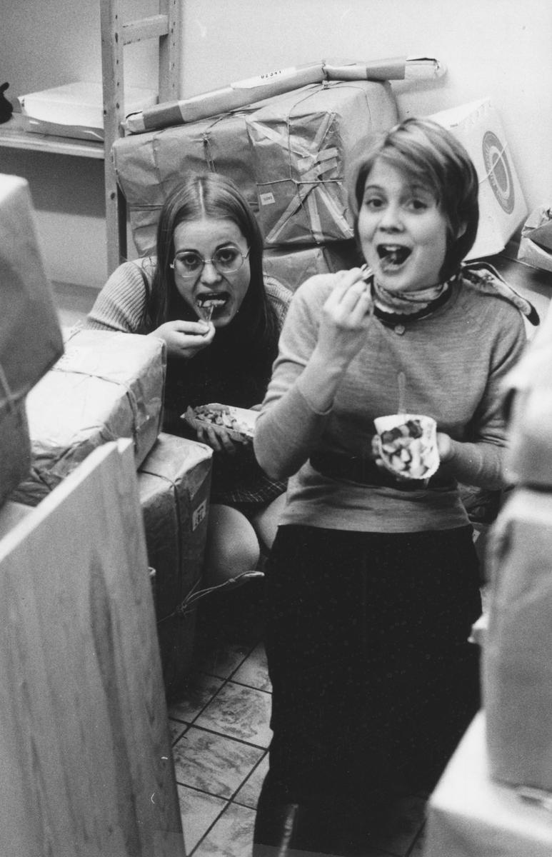 Julruschen på postkontoret Jakobsberg, 1969. Marie-Louise Ericsson och Christina Magnusson, två feriearbetande skolungdomar, tar en paus och äter korv och pommes frites bland alla paketen.