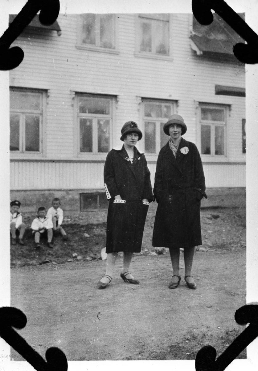 Bildet er tatt utenfor Berlins butikk. Foran Svanhild Hansen og Esther Lein i mørke kåper og hatter.På bena har de sko med reimer over anklene. Guttene i bakgrunnen er Reid Holmen, Rolf og Thore Lein.