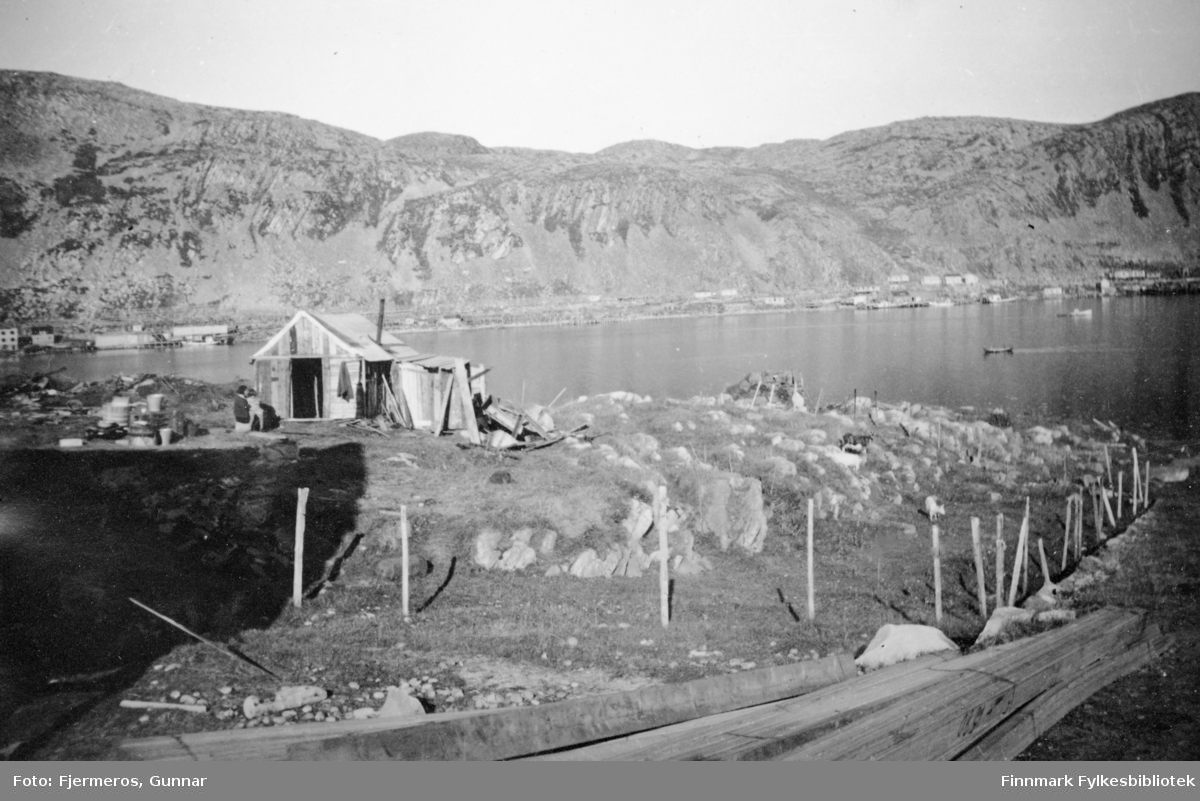 En liten bolig er satt opp av materialer funnet rundt på området. Noen stabler med material ligger i forkant på bildet og boliger står langs strandkanten på andre siden av fjorden. Stedet er ukjent, men bildet er tatt sommeren 1946.