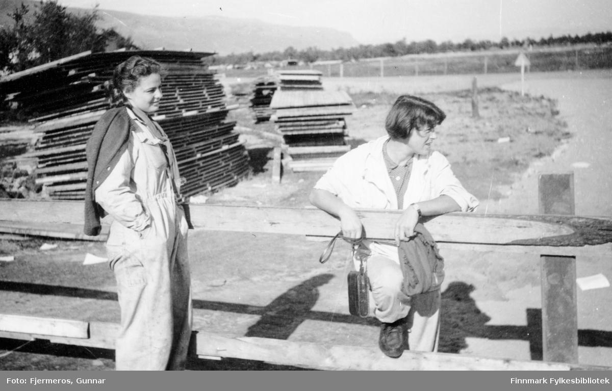 To kvinner fotografert ved gjerdet på Banak flystasjon i Lakselv en sommerdag. Persoene er ukjente og bildet er tatt i august 1946.