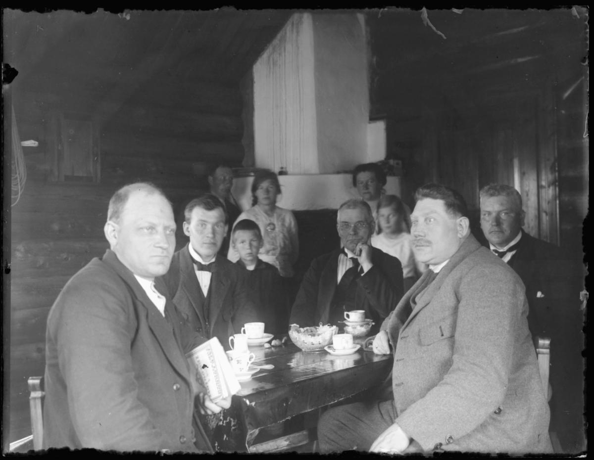 Fem menn sitter rundt et kaffebord. To kvinner og to barn, en gutt og en jente, i bak- grunnen. Helt bakerst i guppen en står en mann og røyker pipe.