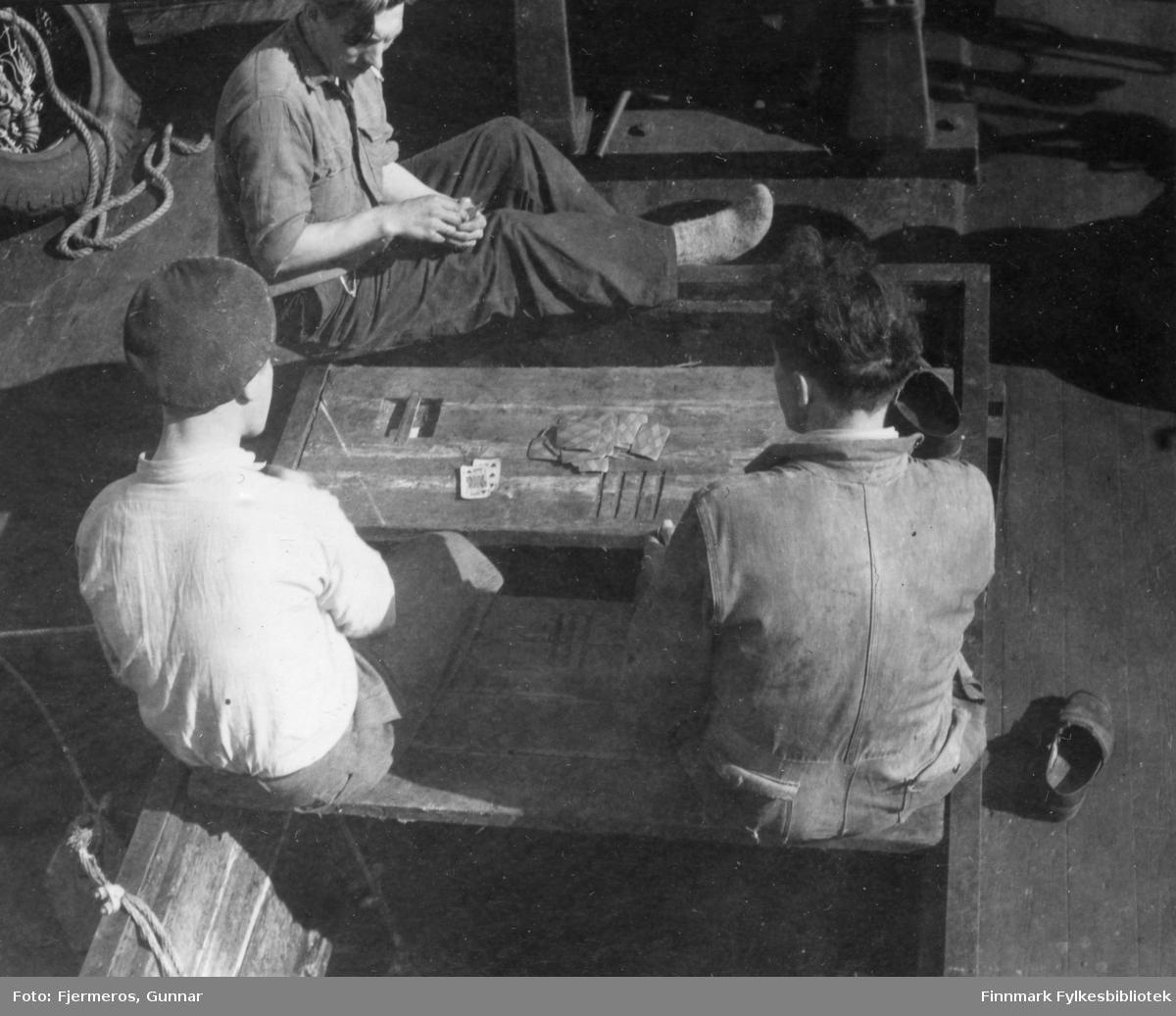 Tre unge menn sitter på dekket til en fiskeskøyte og spiller kort. Menn og båt er ukjent, men bildet er tatt i Laksefjorden våren 1948.