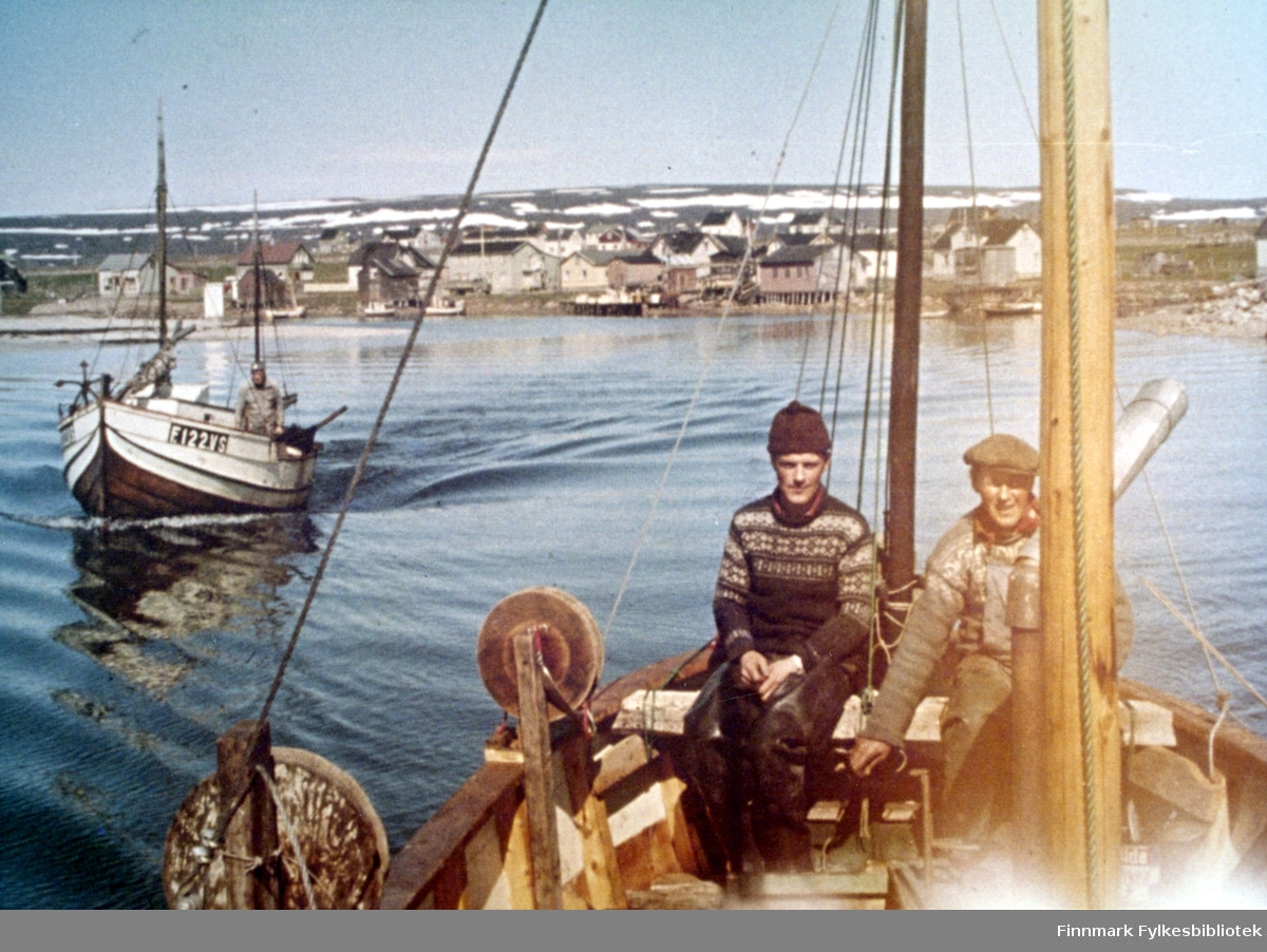 To båter på vei ut til fiskefeltet i Varangerfjorden med Skallelv i bakgrunnen. Den bakerste båten var eid av Einar Huru så det kan være han som er ombord. I båten nærmest sitter, fra venstre Oddvar Basso og Arnulf Bauna som eide båten.