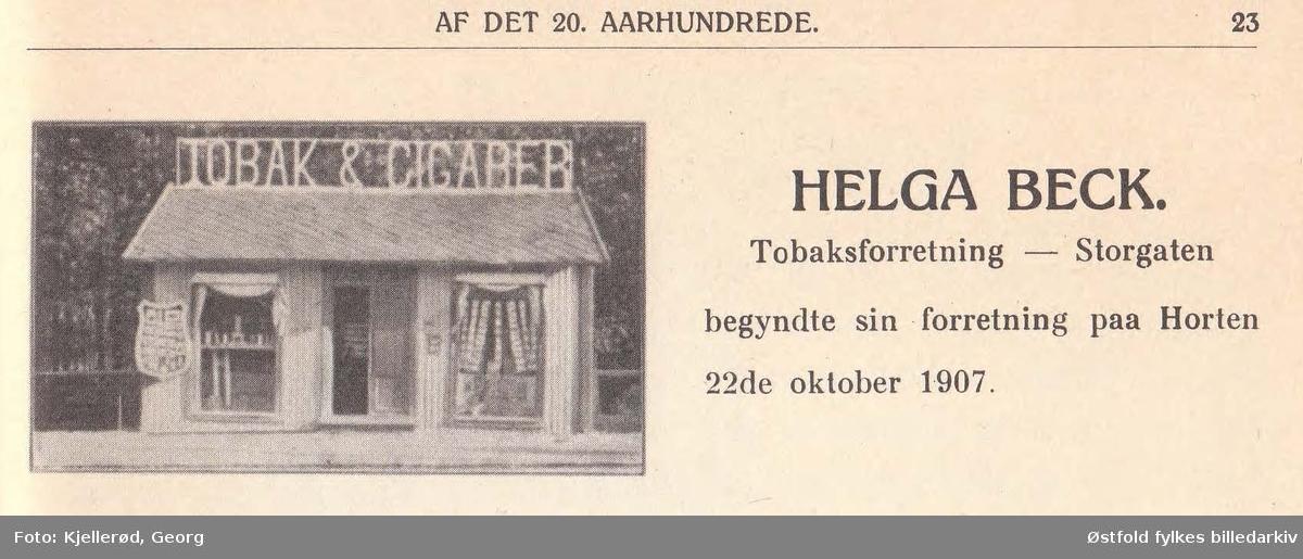"""Horten med bygning for telefon og telegraf i Storgata.   Helt til venstre: Helga Beck, kiosk med reklame for """"Tobak & Cigarer"""" på taket. Helga Beck startet sin butikk 22. oktober 1907 skriver Johan Beck (1911) med tilhørende bilde av nettopp denne tobakksforretningen (lengst unna i bildet).   Borreminne skriver at telefonsentralen var plassert nederst i Storgata i bakermester Olsens gård (murbygningen avbildet).   Bygningen i midten ser ut til å være et bakeri. Folketelling 1910 forteller at Henry Grøstad var bakeren som hadde tilhold her, i 1910 var adressen Storgata 64, senere omgjort til dagens Storgata 2."""