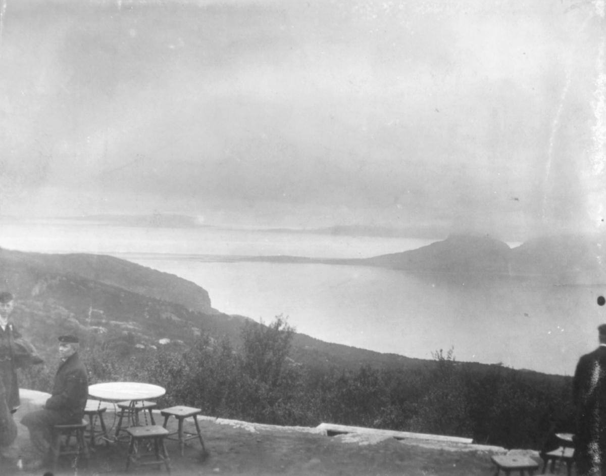 """""""Fra turisthytten. Bodø."""" I venstre hjørne av bilde kan man se et bord med krakker rundt. En mann sitter ved bordet."""