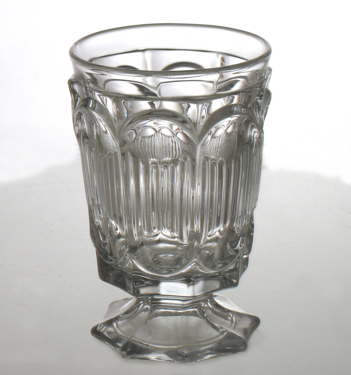 Ølglass, 6 stk.  Pressglass.  8- kantet  fot, lav stett. 8 kantet cupa, (glatt  og rund inni) med innpressede   store ovaler,   riflet  i midtpartiet. Glatt kant. øverst.