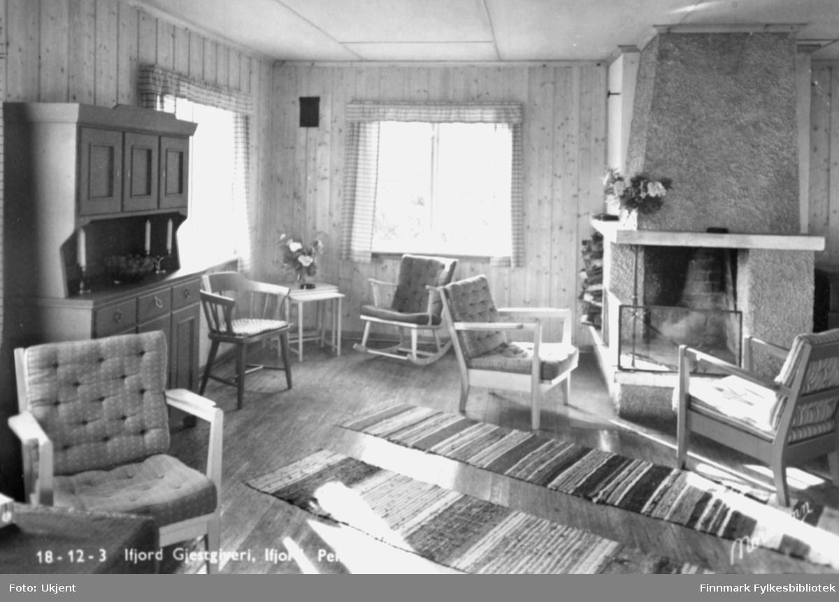 Et bilde tatt inni Ifjord gjestgiveri. På bildet kan man se stoler, matter, vindu, gardiner, ildsted, skap, talgelys og blomster.  Bildet er trolig tatt i løpet av siste halvdel av 1900-tallet.