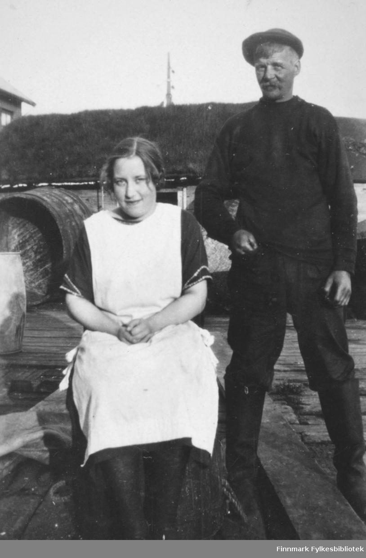 En kvinne og en mann fotografert på en kai, muligens i Kiberg. Kvinnen er Gudrun Bauna og mannen heter muligens Hargala, fornavn ukjent.
