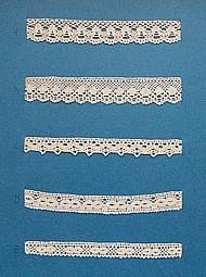 Blått kartongark med fem stycken prover på skånsk knyppling från Gärds härad. Vid varje prov står en stor bokstav. A. 13 x 2 cm, knypplad med 16 par pinnar B. 13 x 2,2 cm, knypplad med 20 par pinnar C. 13 x 1 cm, knypplad mrd 11 par pinnar D. 13 x 1,5 cm, knypplad med 13 par pinnar E. 13 x 1,2 cm, knypplad med 9 par pinnar