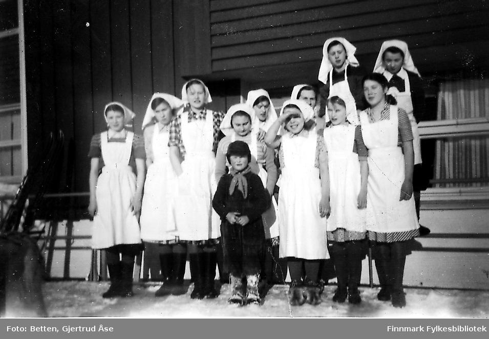 En klasse jenter står på trappa på skolen i Seida. Jentene har på seg hvite forklær og hvite tørkler. Dem er fra Boftsa skole og i husholdopplæring i Seida. En liten gutt står foran dem.