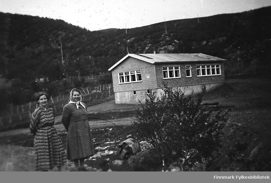 Skolen i Smalfjord. To kvinner står ved skolen. Fra venstre Gjerdrud Betten og fru Dalsbø. Gjerdrud Betten var lærer ved Sieda skole og reiste til Smalfjord for å undervise i handarbeid og skolekjøkken.