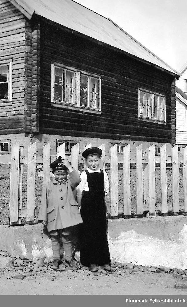 To gutter står på gate ved en tømmerbyggning i Vadsø. Huset tilhører Gjerdrud Betten og gutten til høyre er hennes sønn Bjørn Ottar Betten. Den andre gutten heter Rudolf Betten.