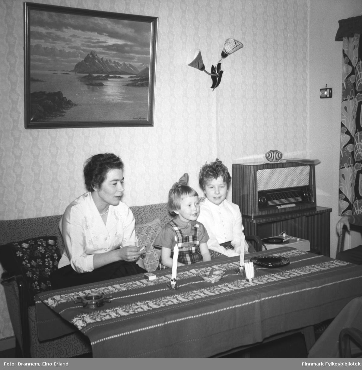 Fra venstre Jenny Drannem, Grete Sørensen og Turid Lillian sitter på en sofa. Det er juletid og bordet er pyntet med to stearinlys og en juleduk