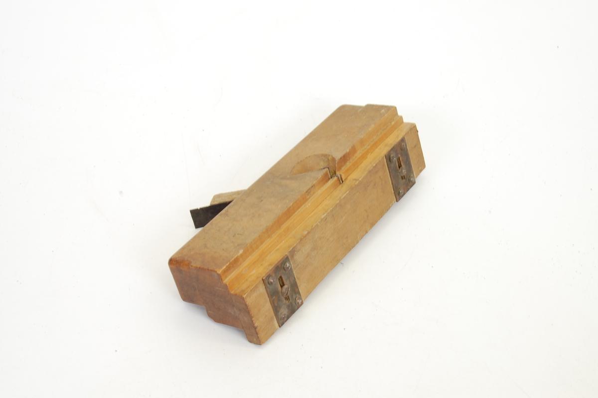 Form: rektangulær trebete, smal, avlang jernstolpe festet i, det er påskrudd to jernbeslag på undersida av høvelen