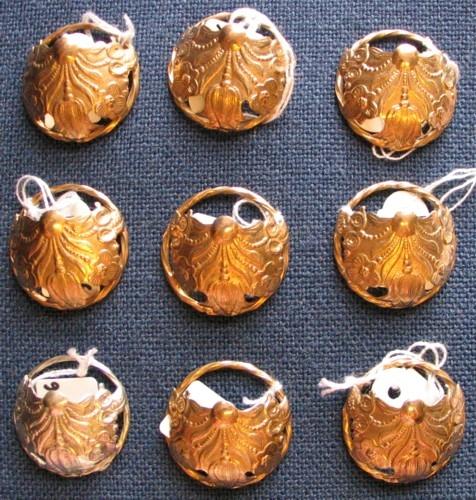 9 stycken silvermaljor, varav 8 förgyllda, med samma stansade motiv med en tulpan i mitten och fyra andra blommor, parvis lika, på ömse sida. Den stansade ovanplattan är fäst mot en vriden ring.