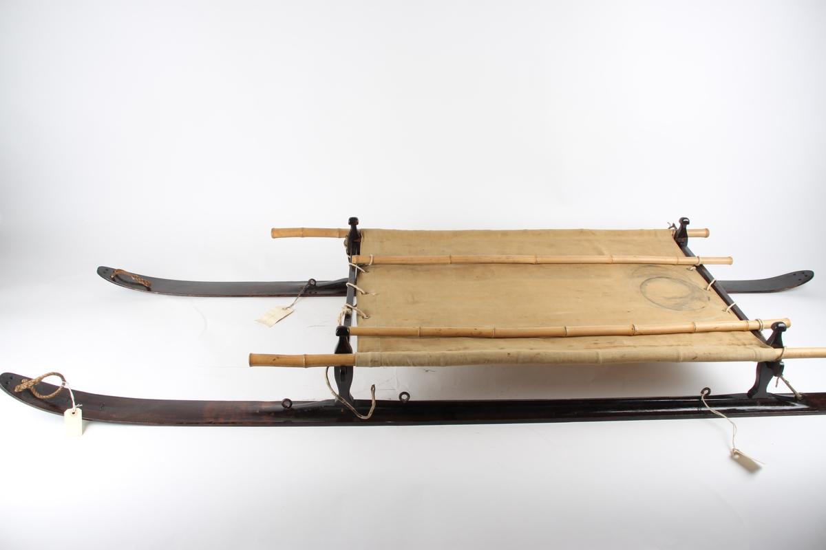 """Skikjelke for en person med meier i tjærebeiset tre. Pulkens """"sete"""" er av seilduk, spent over en ramme av blant annet bambusstenger."""