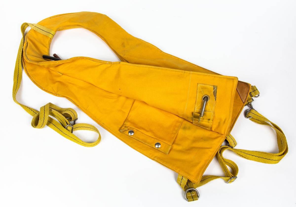 """Flytväst, modell 1, som träs över huvudet och spänns fast runt midjan och under grenen. Munventiler i svart och brun gummislang. Flytvästen är sydd i två lager och har en ficka mellan lagren fram. Flytvästen är tillverkad i ett gult bomullstyg, har en rektangulär skinnbit påsydd fram, stämpel, """"F 1 823"""" på ena sidan, skinnskodd i hörnen nedtill fram. Rem och fästanordning fastsydda nedtill och en längre rem i övre kant."""