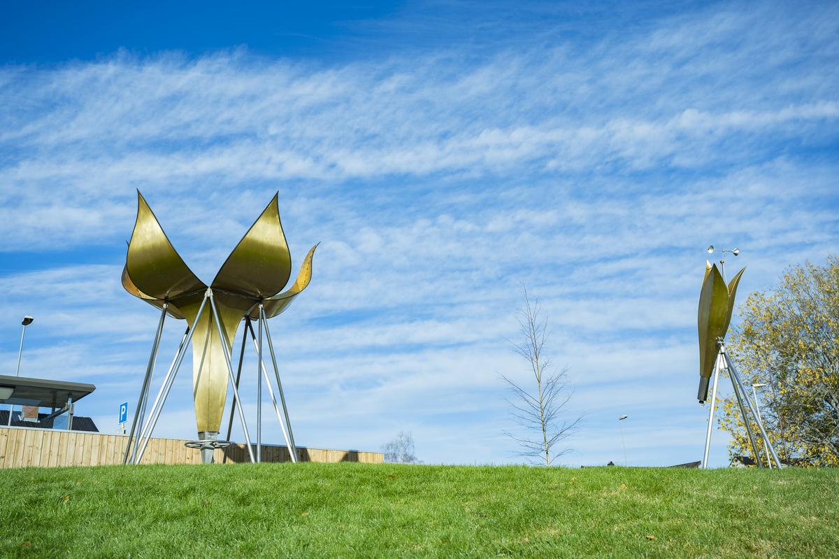 """""""Spir"""" består av to kunstverk som sammen utgjør en helhet. Det største elementet er en høyreist skulptur i metall som kan likne på en slags kuppel eller romskip. Toppen kan åpnes ved å snurre på et hjul som gjør at """"kronbladene"""" brettes til side og skulpturen fremstår som en åpen blomst. Det minste elementet er utformet som en kikkert hvor vindfangere gjør at innmaten snurrer med vinden og utgjør en kaleidoskopisk effekt."""
