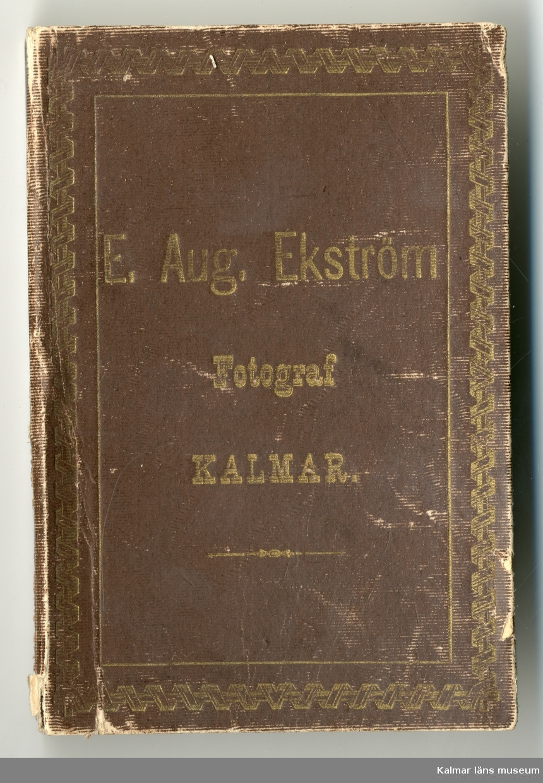 KLM 27830. Ask, för fotoförvaring. Kartong formad som en liten bok, klädd med brunt papper med text i guld: E. Aug. Ekström Fotograf KALMAR. I kartongen 5 fotografier med porträtt, fotograferade av E. Aug. Ekström.