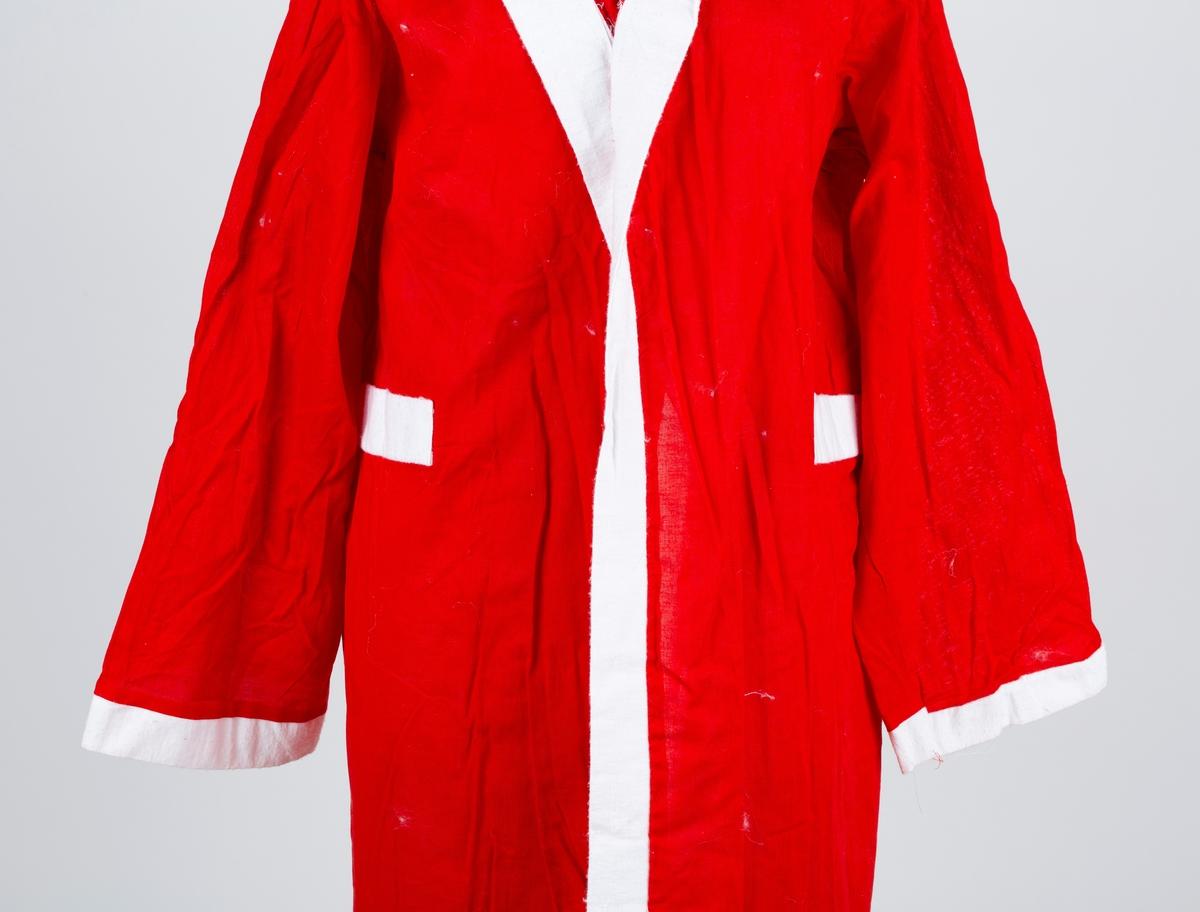 Julenissedrakt i bomull og syntetisk materiale, lang rød frakk med hette, kantet med hvitt stoff, med tilhørende hjemmelaget hvitt skjegg. Snor til belte. Voksen størrelse.